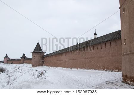 Stone wall of Suzdal monastery winter cloudy day