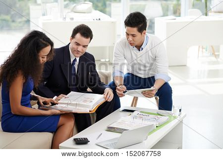 Designers showing catalogue of ideas to businessman