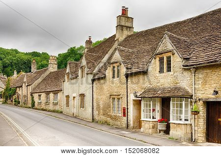 Historic stone homes along street through Castle Combe Village in Wiltshire, England.