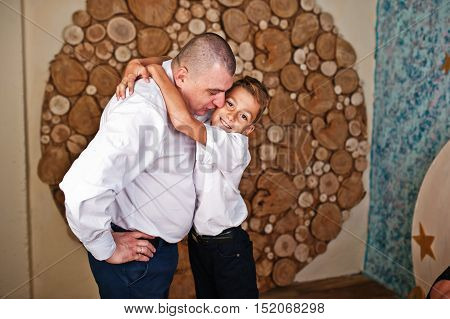 Happy son hugging his father baclground round wooden wall