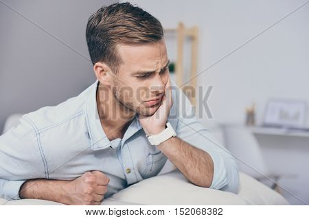 Need a doctor. Handsome young unhappy man closing his eyes and having toothache while sitting in the room.
