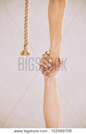 Hands of people holding each other to help