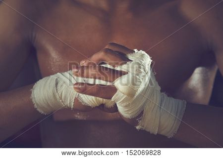 Boxer tape tied around his hand ready to fight.