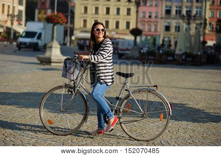 Cute girl in a striped cardigan with bicycle on the street of the ancient city. Sunny warm day. Girl has an excellent mood. She smiles.