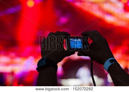 Hands Holding Smartphone with Stage Lights on Background