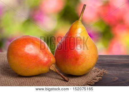 two pears on a dark wooden table with a blurred background.