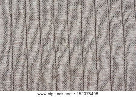 Background of beige textured draperies. Knitted pattern.