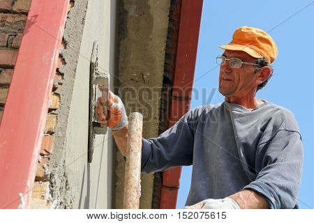 Builder Worker At Plastering Facade Work. Mature contractor plasterer working outdoors.