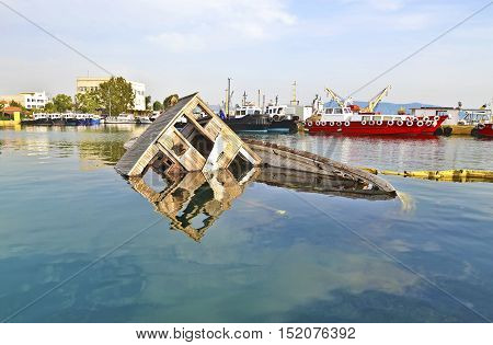 sunken boat reflected on water at Eleusis Greece