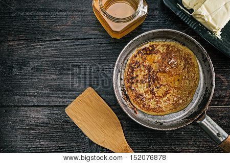 Frying pan with prepared pancake on the kitchen desk