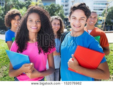 Group of five happy latin american caucasian and african students outdoor in the city in summer