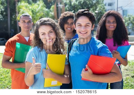 Group of five smart latin american caucasian and african students outdoor in the city in summer