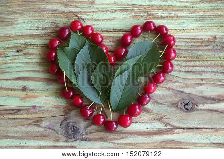 fresh seasonal cherry berry fruit red color with healthy vitamins on wooden or wood table laying in shape of heart as love symbol of valentines day holiday with green leaves