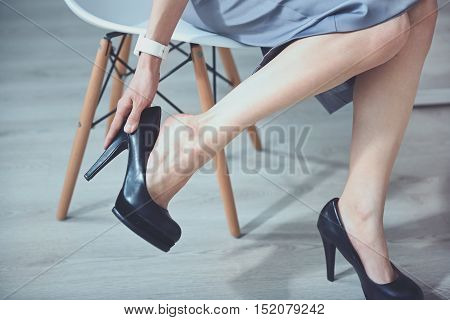 Unsuitable shoes. Young slim woman sitting on the chair and taking off heels