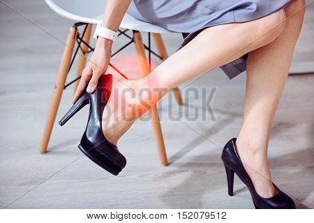 I hate hills. Close up of young slim woman sitting on the chair and having pain in the legs while taking off her shoes.