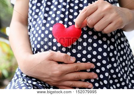 Pregnant women wear navy blue maternity clothes and a red heart symbol placed on belly.