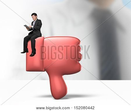 Man Holding Tablet And Sitting On Red Thumb Down