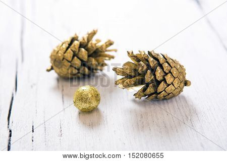 Brilliant gold cones like christmas decoration. Yellow cones isolated on white wooden background.