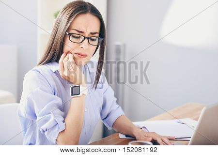 Can nor resist it. Serious young woman using laptop and suffering from toothache.