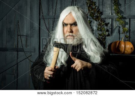 Angry man witch in black robe with white long hair and beard hold hatchet near finger in wooden house