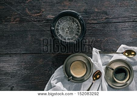 Metal vintage cups of coffee  and ashtray on the wooden table. Flat lay
