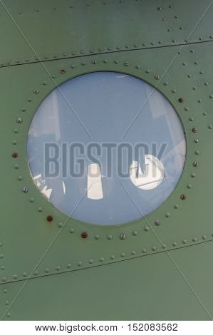 Window in old airplane aluminum background detail of a military porthole aircraft