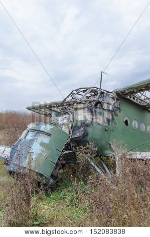 Old broken green russian airplane on the field
