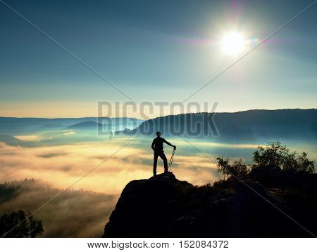 Tall Backpacker With Poles In Hand. Sunny Misty Daybreak In Rocks