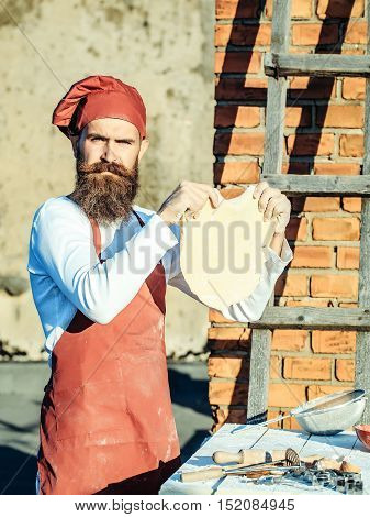 Man cook chef in red hat and apron white uniform with bearded handsome face holding dough in hands on brick wall with ladder background outdoor