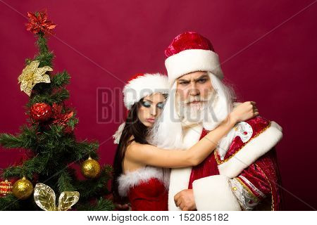 Tender girl in new year red suit and hat embraces santa claus man near Christmas tree