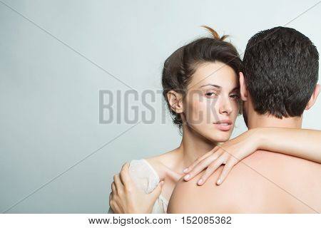 young sexy couple of muscular man embracing with back and pretty woman or girl with brunette hair in studio on grey background copy space