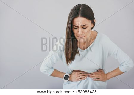 Dull pain. Beautiful young woman biting her lip and closing her eyes while standing against white background