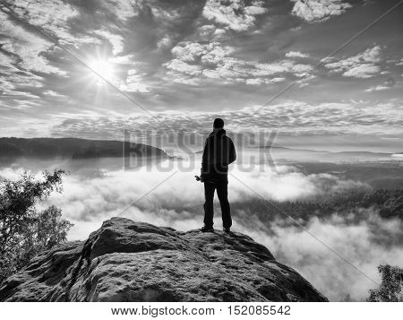 Photographer With Folden Tripod On End Of Cliff Thinking. Misty Landscape