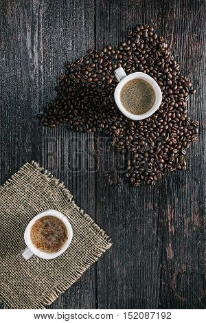 White ceramic cups of coffee on the table covered with coffee beans. Flat lay
