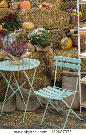 coffee table and chair near haystack decorated with flowers, pumpkins, lavender. autumn fall stylish look