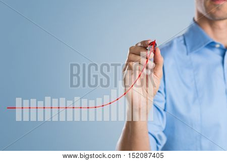 Close up of businessman using marker to draw a growing graph. Closeup of man hand holding marker isolated on a blue background. Successful businessman increasing his business.