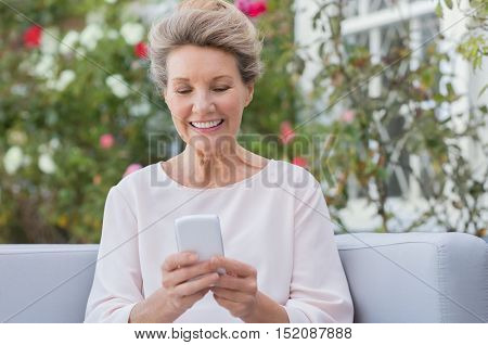 Senior woman messagging with mobile phone while sitting on sofa in the garden. Older woman texting a phone message with her new smartphone.