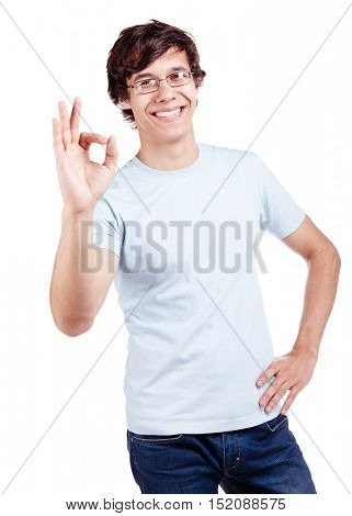 Young hispanic man wearing glasses, blue t-shirt and jeans showing A-ok hand gesture and smiling isolated on white background - success concept