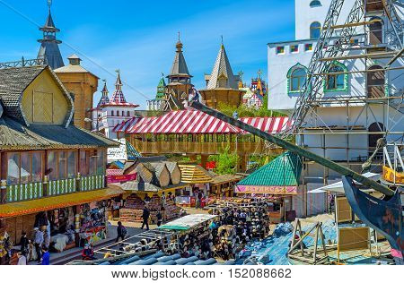 MOSCOW RUSSIA - MAY 10 2015: The view on Russian izba houses Izmailovsky Market stalls towers of Kremlin through the prow of the ship's replica on May 10 in Moscow.