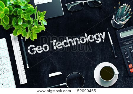 Geo Technology. Business Concept Handwritten on Black Chalkboard. Top View Composition with Chalkboard and Office Supplies. 3d Rendering. Toned Image.