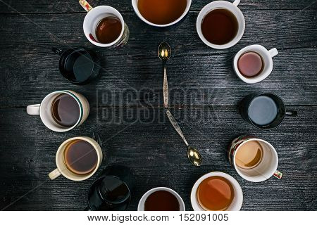 Teaspoons reading five o clock in the middle of the circle of various tea cups and mugs. Flat lay
