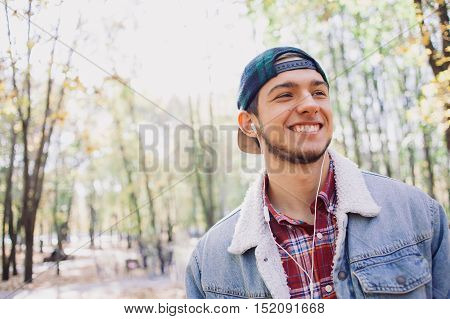 Smiling man listening to music in an autumn park. Student in a denim jacket and a red shirt in the cap