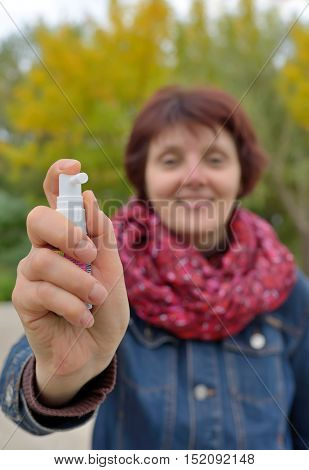 Woman using throat spray in cold season