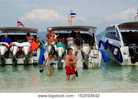 Phuket Thailand - January 16 2007: Visitors leaving small touring boats wade ashore to sandy Khai Island