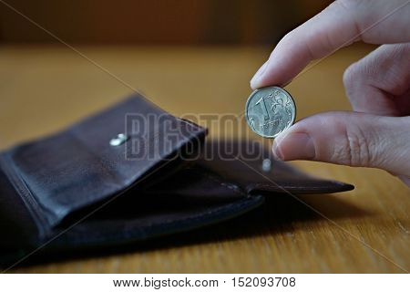 Male hand holding a silver Russian Rouble coin (currency in Russia, Russian Ruble or Rouble, RUB) and withdrawing that from the brown leather wallet
