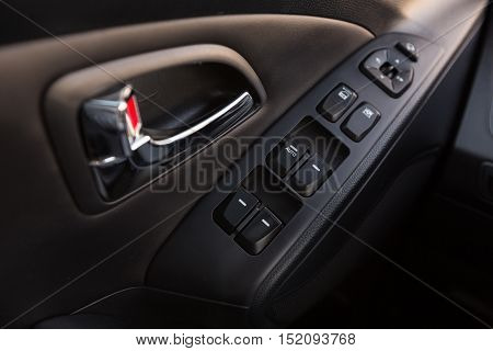 Closeup of a Door Control Panel and Handle in a Modern Car