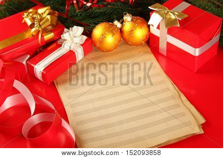 Christmas card with gift boxes and Christmas ornaments and Christmas tree branches and Christmas balls. Paper sheets stave