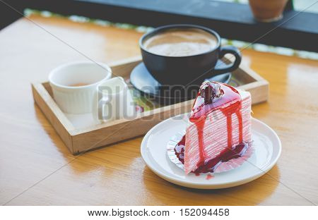 strawberry crape cake and hot coffee. strawberry crape cake with strawberry sauce. strawberry crape cake in cozy outdoor cafe.(selective focus)