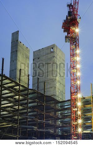 South Boston Massachuetts USA - October 13 2016: Construction crane illuminated in morning twilight at 50 Liberty project in South Boston