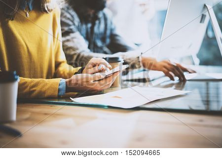 Closeup of young coworkers working with electronic gadgets in sunny office.Man typing on the desktop keyboard and woman using her mobile phone. Horizontal, blurred
